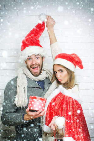 Young funny Christmas couple in red santa claus hats of handsome man with gift box and pretty sexy girl or beautiful woman on white brick wall under snow and snowflakes