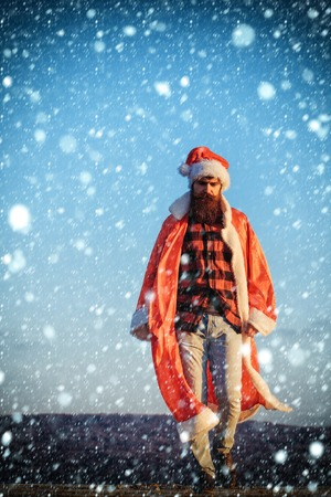 young handsome bearded bad santa claus man with long beard in checkered shirt jeans and red new year hat in christmas or xmas coat outdoor on blue sky background under snow and snowflakes, copy space