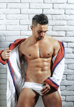 macho: Handsome man or muscular macho, bodybuilder, with sexy, muscle torso, body, with six packs and abs, in sexi underpants and bathrobe poses on white brick wall