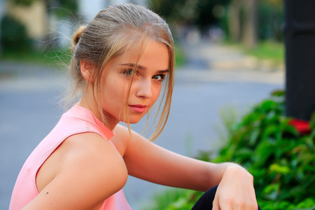 girl tied: Pretty sexy young woman or girl with tied in bun blonde hair in pink shirt with cute serious face on blurred background Stock Photo