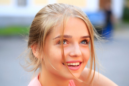 girl tied: Pretty sexy young woman or girl with tied in bun blonde hair in pink shirt with cute face smiling on sunny day