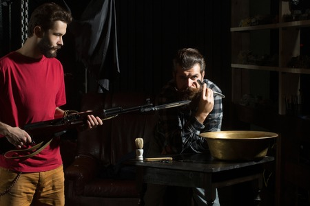 Two men, handsome, bearded hipsters, with beards and moustaches hold rifle with bayonet and razor with blade on dark background Stock Photo