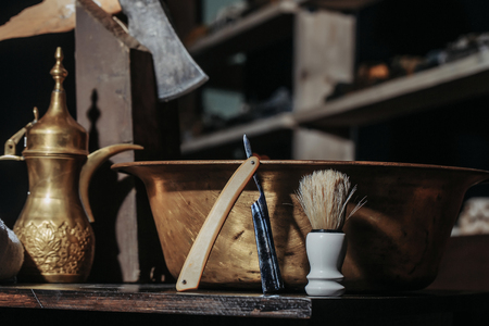Vintage barber or shaver tools on wooden table. Old razor with cutthroat blade, copper basin, water jug, axe and shaving brush in barbershop or hairdressing saloon Stock Photo