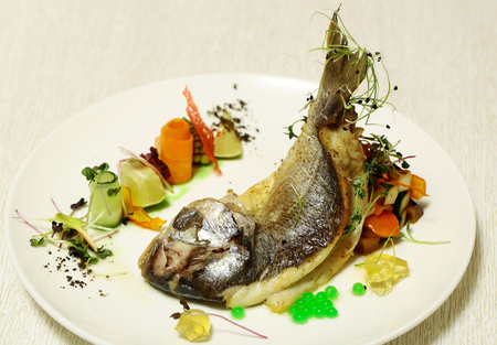 Roasted fish served with colorful vegetables, zucchini, green jelly caviar, carrot, lime, sprouts on plate on white background. Modern molecular gastronomy