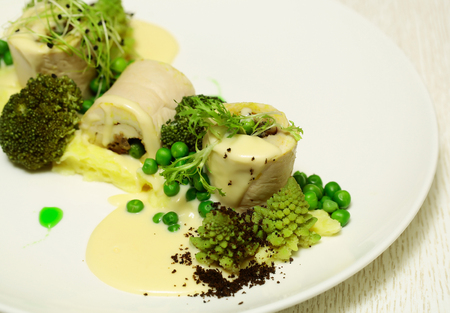 broccoli sprouts: Fish fillet rolls with mashed potato, green vegetables, pea, broccoli, sprouts, and sauce on plate on white background. Modern molecular gastronomy Stock Photo
