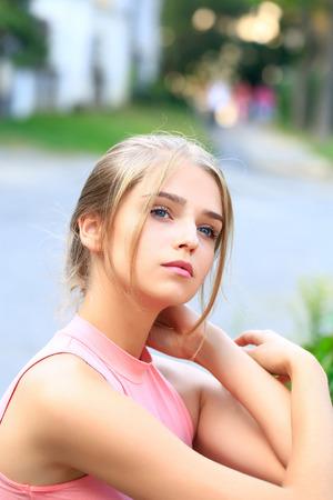 bollos: Mujer joven bastante atractiva o niña con moño atado en el pelo rubio en camisa de color rosa con la cara linda en el fondo borroso