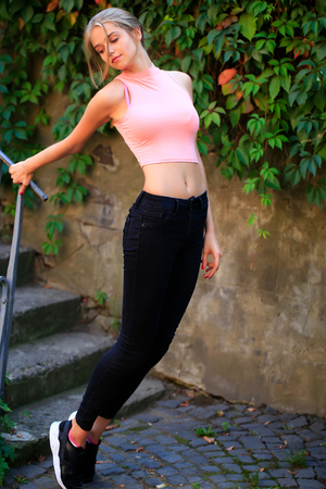 Pretty sexy young woman or sport girl with tied in bun blonde hair in pink shirt with cute face holding by stair and bent with green ivy wall on background