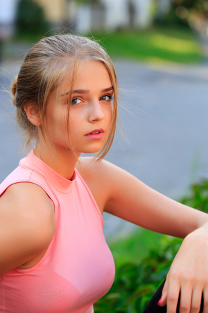 tied in: Pretty sexy young woman or girl with tied in bun blonde hair in pink shirt with cute serious face on blurred background Stock Photo