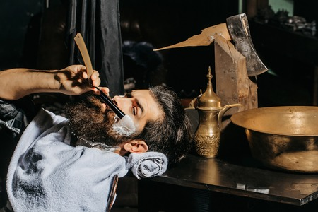Handsome bearded man, hipster, brunette with beard and moustache has shave in barbershop. Barber works with vintage razor, shaving brush and foam Stock Photo