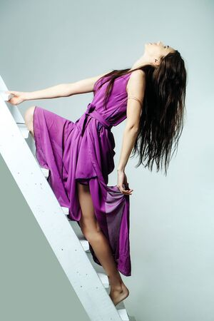 young pretty woman or cute sexy girl with long brunette hair in violet fashionable dress stands on white ladder or stairs in studio on grey background