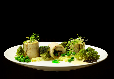 broccoli sprouts: White fish fillet rolls with mashed potato, green vegetables, pea, broccoli, sprouts, and sauce on plate isolated on black background. Modern molecular gastronomy