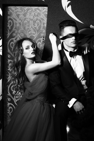 young couple of handsome man in suit and bow with pretty sexy woman in elegant evening dress with skirt and long curly hair, black and white