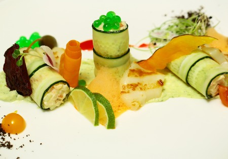 Stuffed zucchini rolls, vegetables, green caviar and sprouts with source and foam in warm colors on plate on white background. Modern molecular gastronomy Stok Fotoğraf