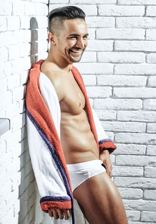 Happy handsome man or muscular macho, bodybuilder, with sexy, muscle torso, body, with six packs and abs, in sexi underpants and bathrobe smiles on white brick wall Stock Photo