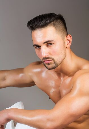 Handsome man or muscular macho, bodybuilder, with sexy, wet, muscle torso, body, chest and hands poses on grey background Stock Photo