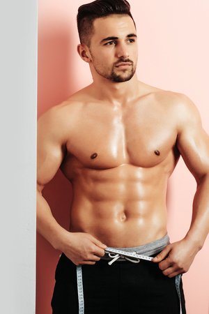 muscle belly: Handsome man or muscular macho, bodybuilder, with sexy, muscle torso, body, with six packs and abs poses on pink background with tape measure on belly. Dieting and healthy lifestyle