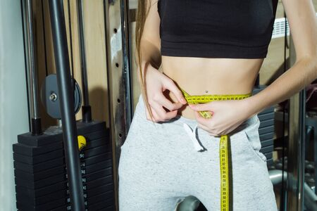 perfect waist: Fit woman measuring perfect shape of beautiful waist with tape measure after sport training, workout, in fitness gym. Healthy lifestyle concept Foto de archivo