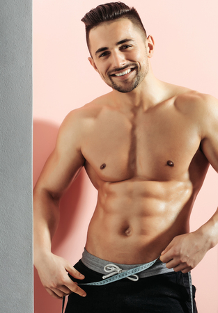 muscle belly: Handsome smiling man or muscular macho, bodybuilder, with sexy, muscle torso, body, with six packs and abs poses on pink background with tape measure on belly. Dieting and healthy lifestyle