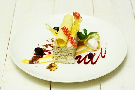Delicious piece of cake with wafer roll, caramelized sugar candy, cream, berry, mint and sweet, dessert sauce on plate on white background. Modern molecular gastronomy