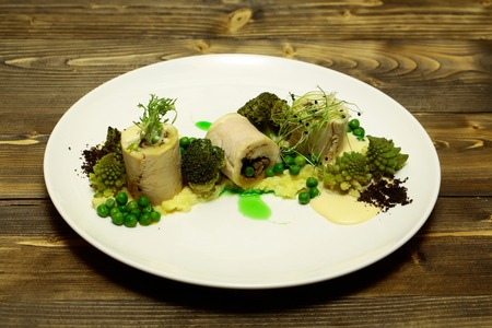 White fish fillet rolls with mashed potato, green vegetables, pea, broccoli, sprouts, and sauce on plate on wooden background. Modern molecular gastronomy