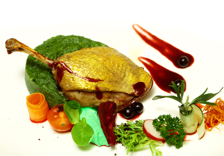 Roasted confit duck leg, pestle, on green puree with vegetable, herbs and red berry sauce on plate on white background. Modern molecular gastronomy Stock Photo