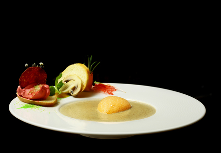 Delicious soup or source with yellow foam served with french bread and sausage slices, chips, vegetables and herbs on plate isolated on black background. Modern molecular gastronomy
