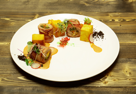 pancetta cubetti: Rolled ham or bacon with yellow red cubes served with vegetables and sauce on white plate on wooden background. Modern molecular gastronomy