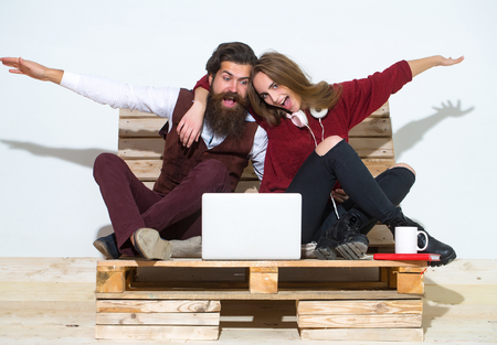 Young happy couple spend time together on wooden pallet sofa. Handsome man, bearded hipster with beard uses laptop, computer. Pretty girl or beautiful woman reads book Stock Photo