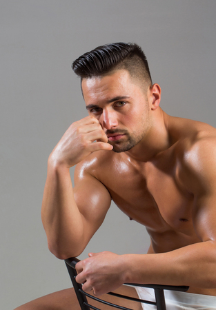 Handsome man or muscular bodybuilder, macho, with sexy, muscle torso, body, with six packs and abs, triceps, biceps, with oily skin in white sexi underpants sits on chair on grey background
