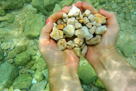 rock bottom: Woomans hands holding small sea stones under water on rocky seabed background. Stock Photo