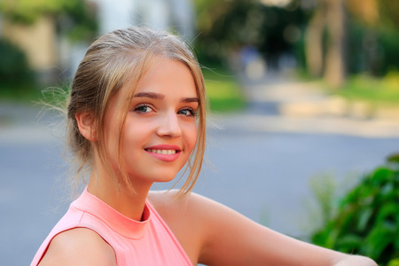 Pretty sexy young woman or girl with tied in bun blonde hair in pink shirt with cute face smiling on sunny day