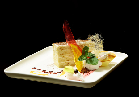 Delicious piece of cake with red caramelized sugar candy, cream, fruit, mint and sweet, dessert sauce on white plate isolated on black background. Modern molecular gastronomy