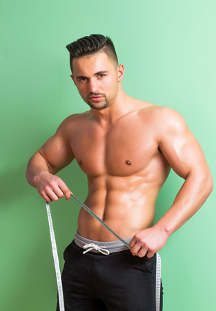 sexi: Handsome man or muscular macho, bodybuilder, with sexy, muscle torso, body, with six packs and abs poses on green background with tape measure on belly. Dieting and healthy lifestyle