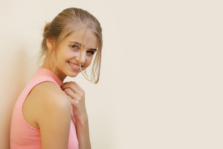 desire: Pretty sexy cute young woman or girl with blonde hair tender hand in pink shirt smiling on beige background