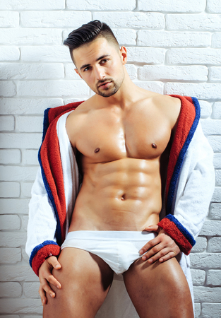Handsome man or muscular macho, bodybuilder, with sexy, muscle torso, body, with six packs and abs, in sexi underpants and bathrobe poses on white brick wall