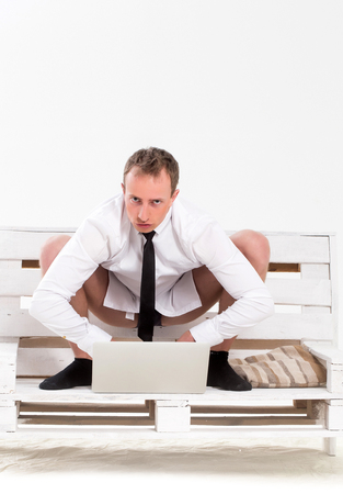 computer isolated: young serious handsome man or businessman working on portable laptop or computer in shirt, socks and tie, sits on wooden bench at home isolated on white background Stock Photo
