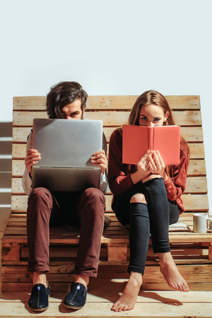 uses a computer: Young couple spend time together on wooden pallet sofa. Handsome man, bearded hipster with beard uses laptop, computer. Pretty girl or beautiful woman reads book