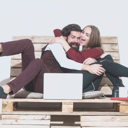uses: Young happy couple spend time together on wooden pallet sofa. Handsome man, bearded hipster with beard uses laptop, computer. Pretty girl or beautiful woman reads book Stock Photo