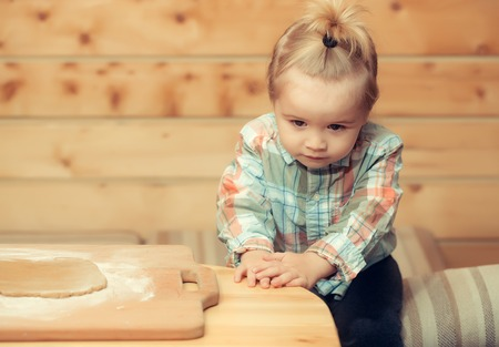 adorable small child chef or cute baby boy in fashionable chekered shirt cooking on board flour and dough on wooden background, copy space Stock Photo