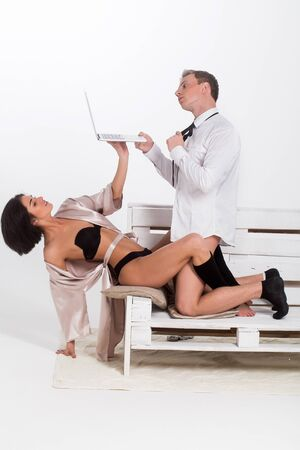 young couple of handsome man or businessman and pretty woman working on portable laptop or computer in shirt, socks, tie, lingerie and gown sits on wooden bench isolated on white background Stock Photo
