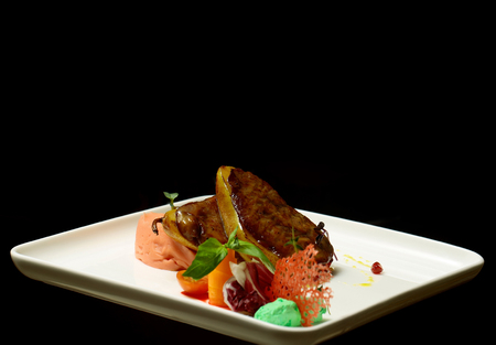 Grilled meat fillet on pear with vegetables, red chips, salad, colorful puree on square plate isolated on black background. Modern molecular gastronomy