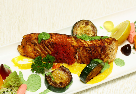 fish sauce: Grilled fish fillet and vegetables, zucchini, lemon, herbs and colorful jelly sauce on rectangular plate on white background. Modern molecular gastronomy