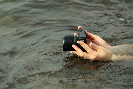 digicam: Female hands hold modern black digital camera or digicam over sea or ocean water surface outdoors on grey background