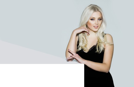platinum hair: pretty girl or cute smiling woman with long platinum blonde hair and fashionable makeup on face in sexy glamour black dress on white and grey background, copy space