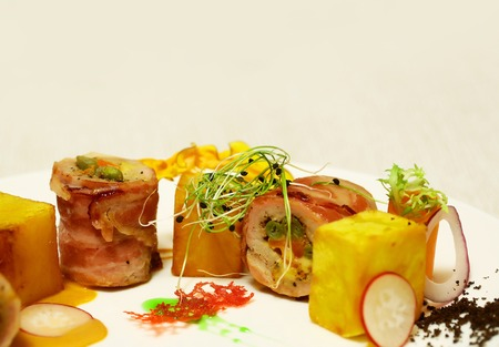 Rolled ham or bacon with yellow red cubes served with vegetables and sauce on plate on white background. Modern molecular gastronomy Stock Photo