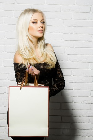 pretty girl or cute woman with long platinum blonde hair and fashionable makeup on face in sexy lace black dress with shopping bag on white brick wall background