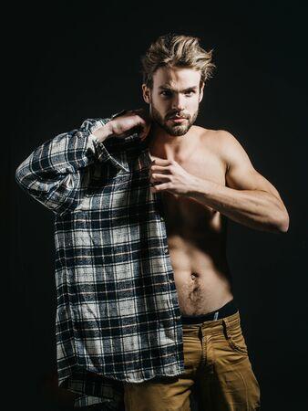 nackter junge: Sexy junge gut aussehend nackter Mann mit dem unordentlichen Haar, in beige Hose trägt kariertes Hemd auf dunklem Hintergrund Lizenzfreie Bilder