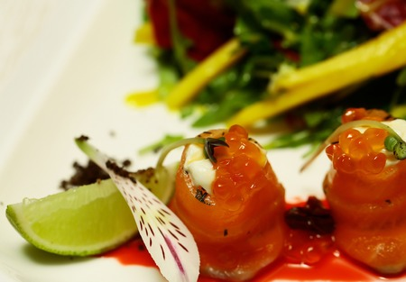 Delicious red fish or salmon rolls with jelly orange caviar and green salad mix on plate on blurred colorful background. Modern molecular gastronomy