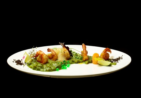 Grilled shrimps or prawns with green pea puree and jelly caviar, vegetables and herbs on plate isolated on black background. Modern molecular gastronomy