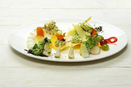 Delicious snack or platter with blue, soft, firm, aged cheese, potato chips, grapes, carrot, radish, salad on plate on white background. Modern molecular gastronomy Stock Photo